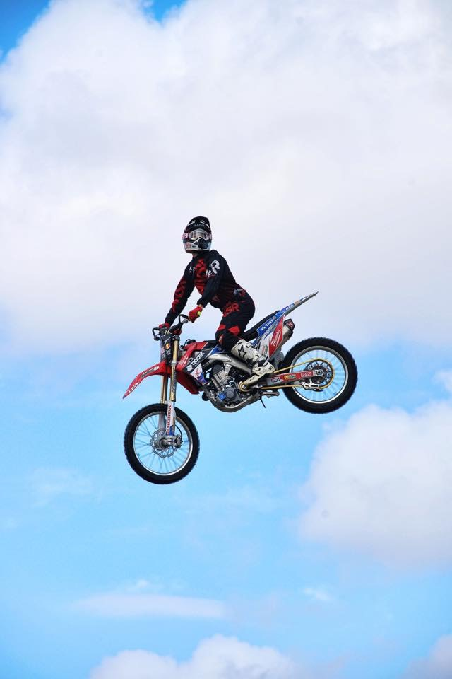 An airborne motorcycle and its rider with the backdrop of a light blue sky and white clouds.