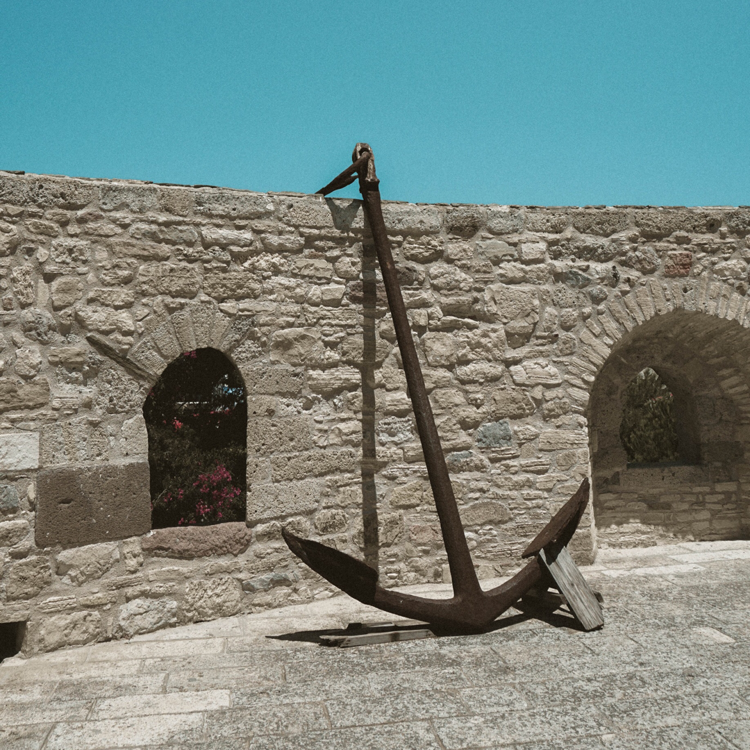 A large anchor thrown over the top of a castle wall.