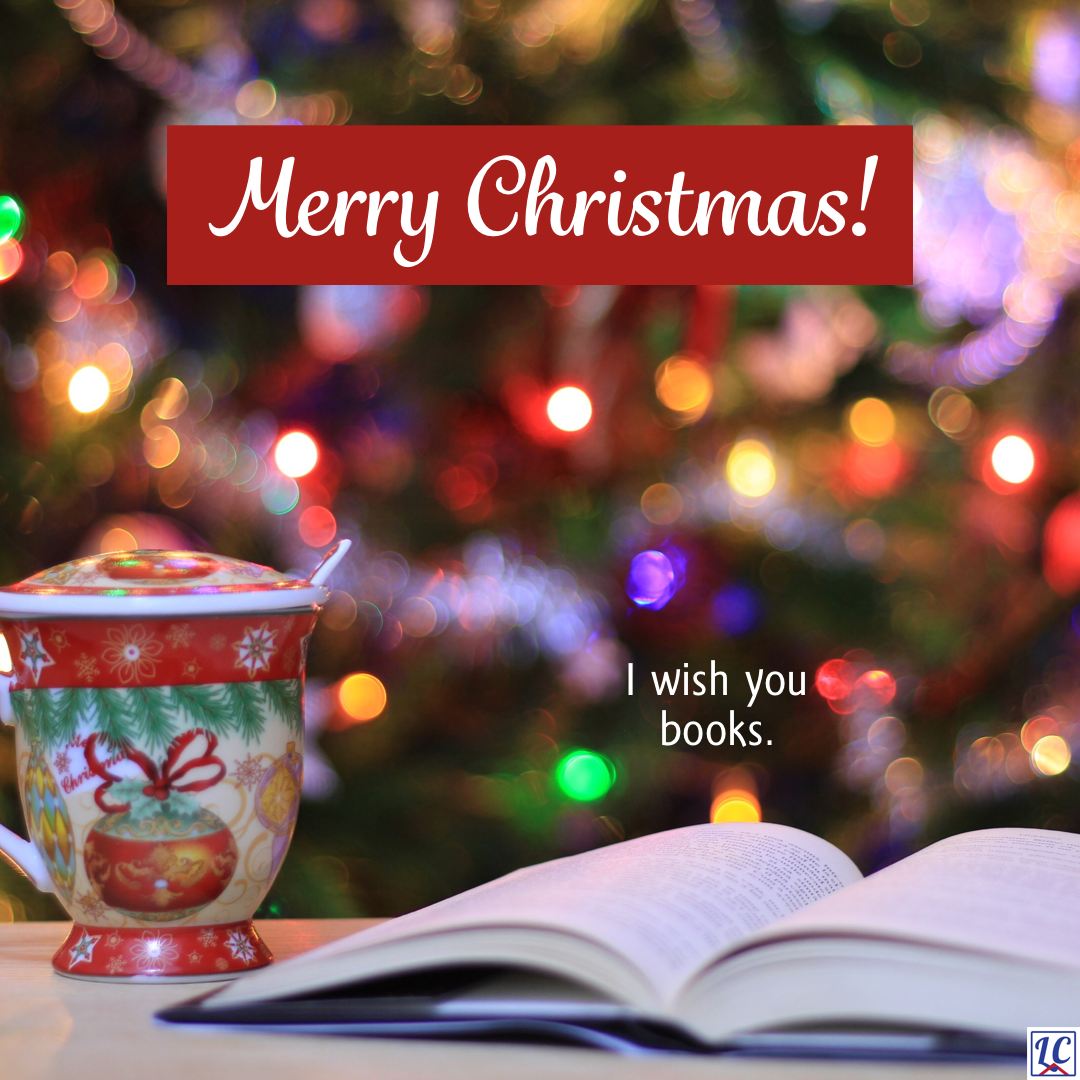 An open book on a table beside a Christmas-themed mug in front of a brightly lit Christmas tree. Caption: Merry Christmas! I wish you books.