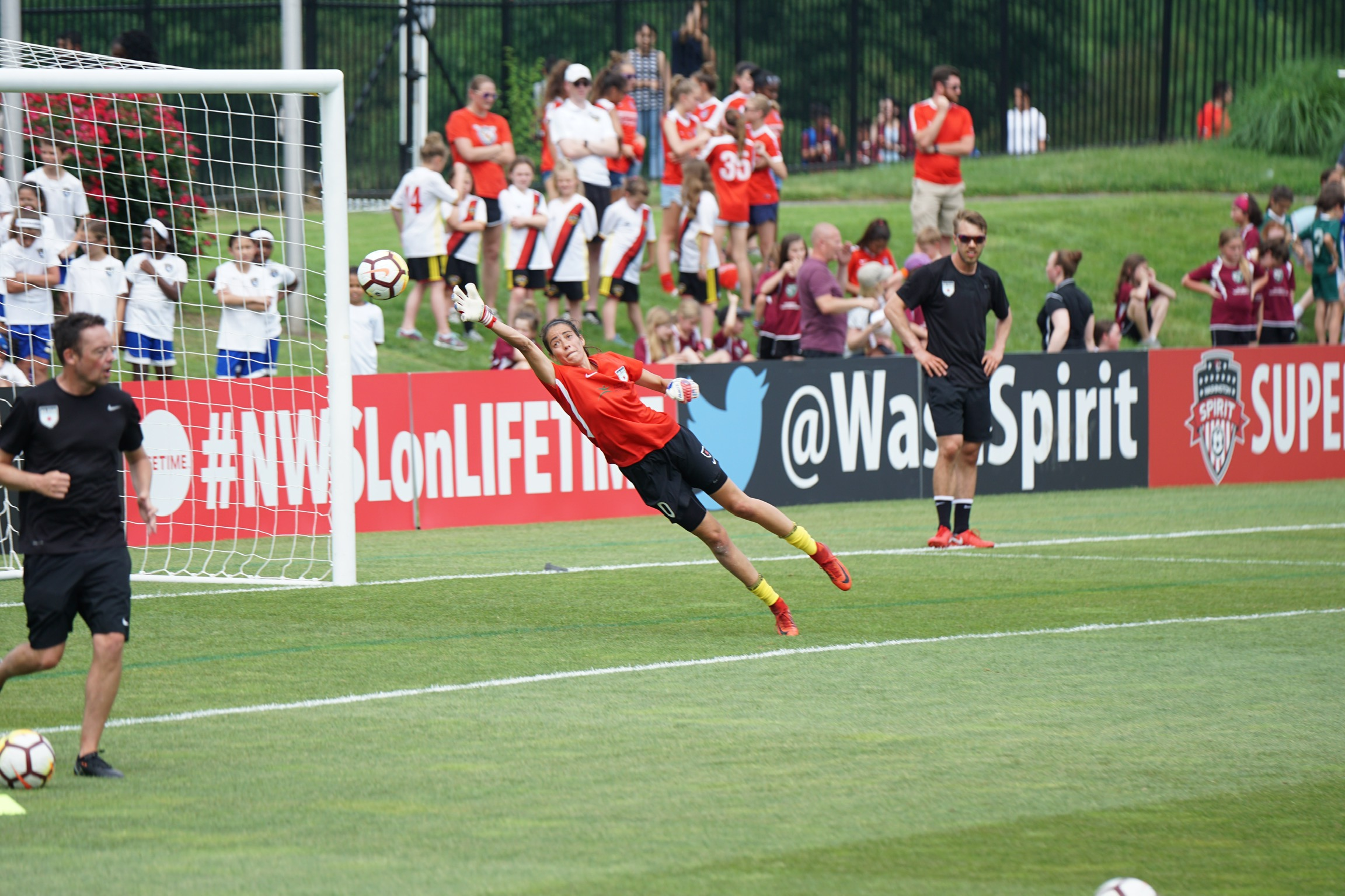A soccer player elevated at a 45 degree angle from the ground, reaching for a soccer ball in front of the net and a crowd of onlookers on the sidelines.