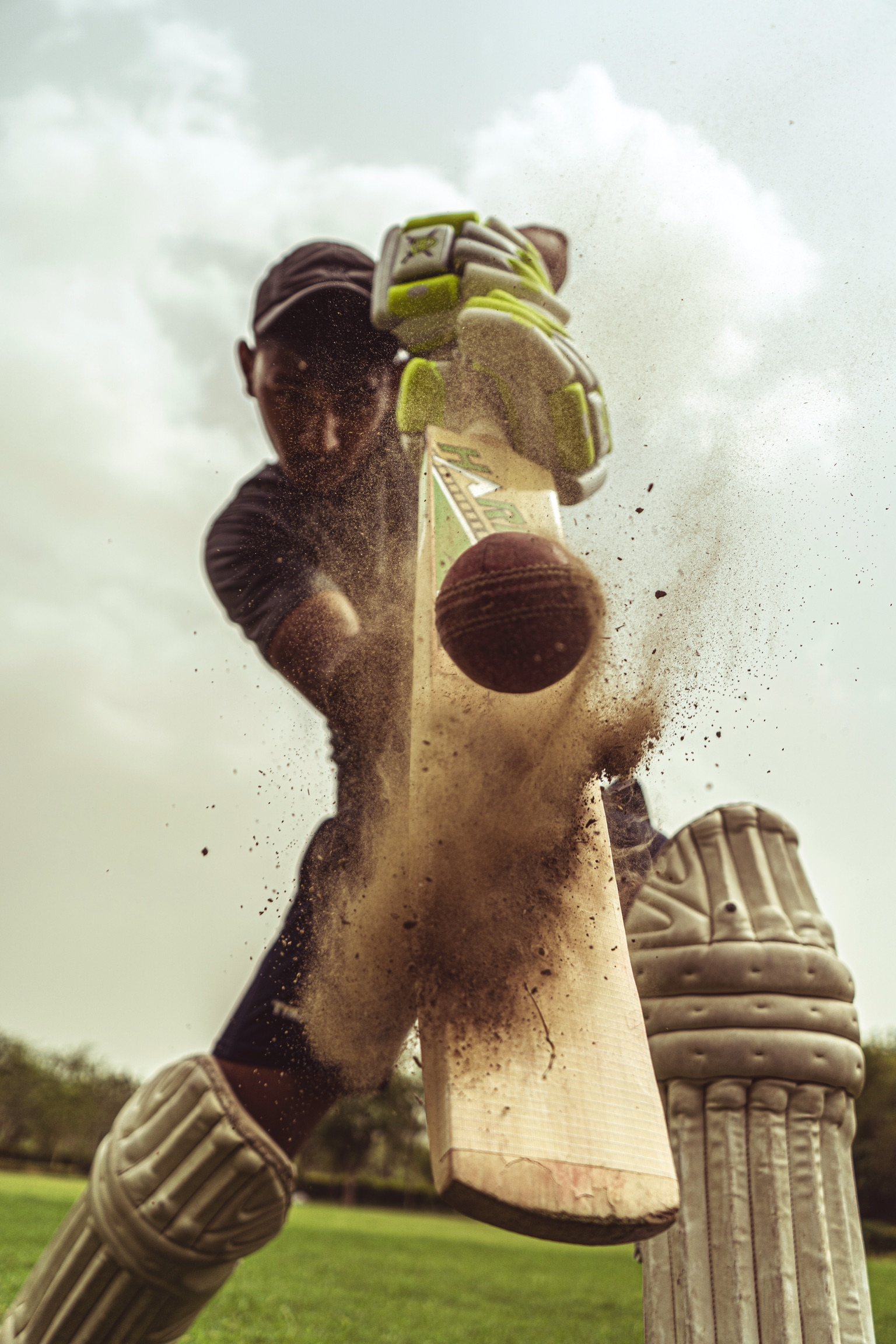 A young man stirring up dirt while hitting a cricket ball with a bat.