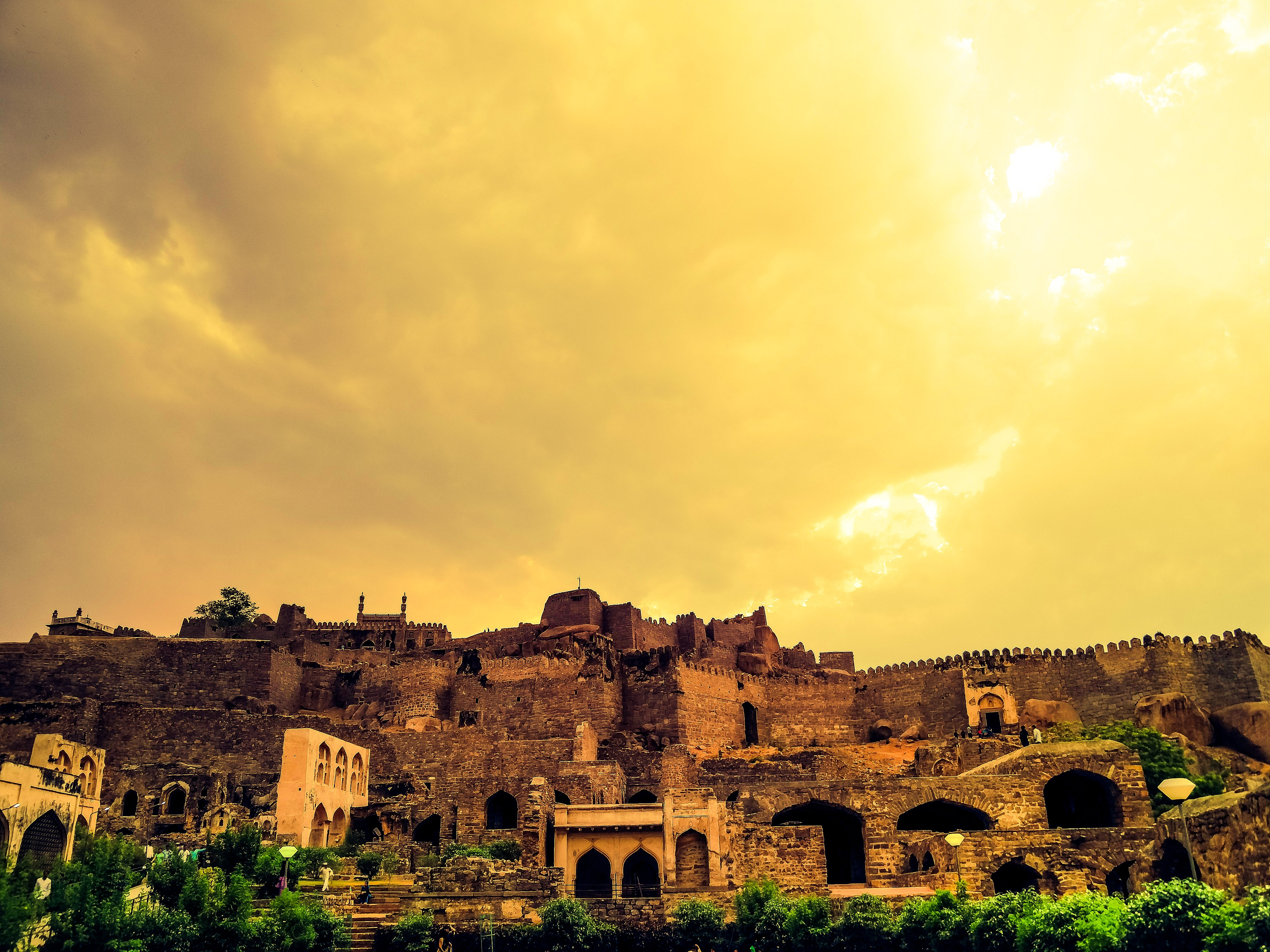 Ancient buildings bathed in a golden glow under a yellow sky.