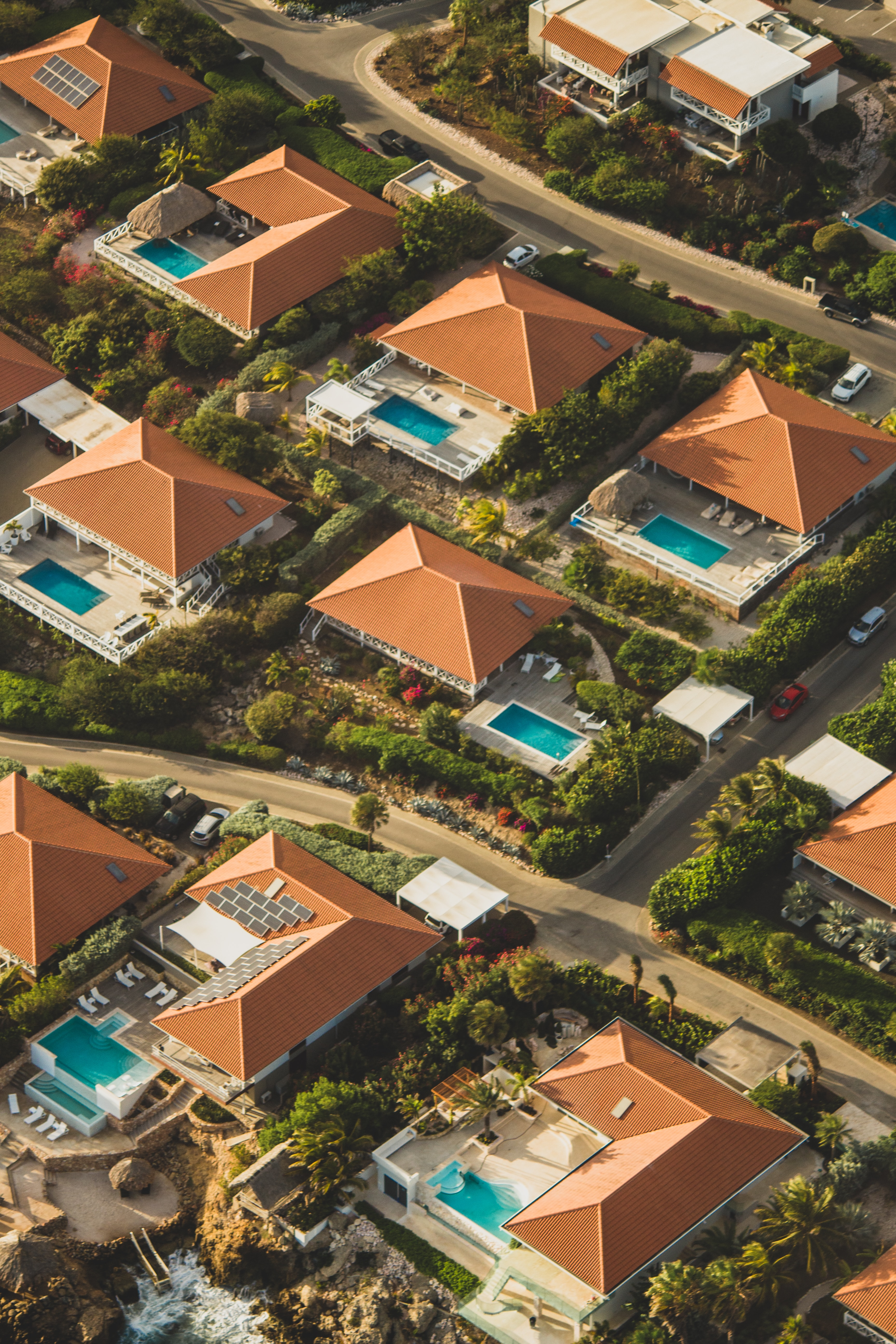 A residential area where all the homes have the same terracotta roofs and rectangular, turquoise pools.