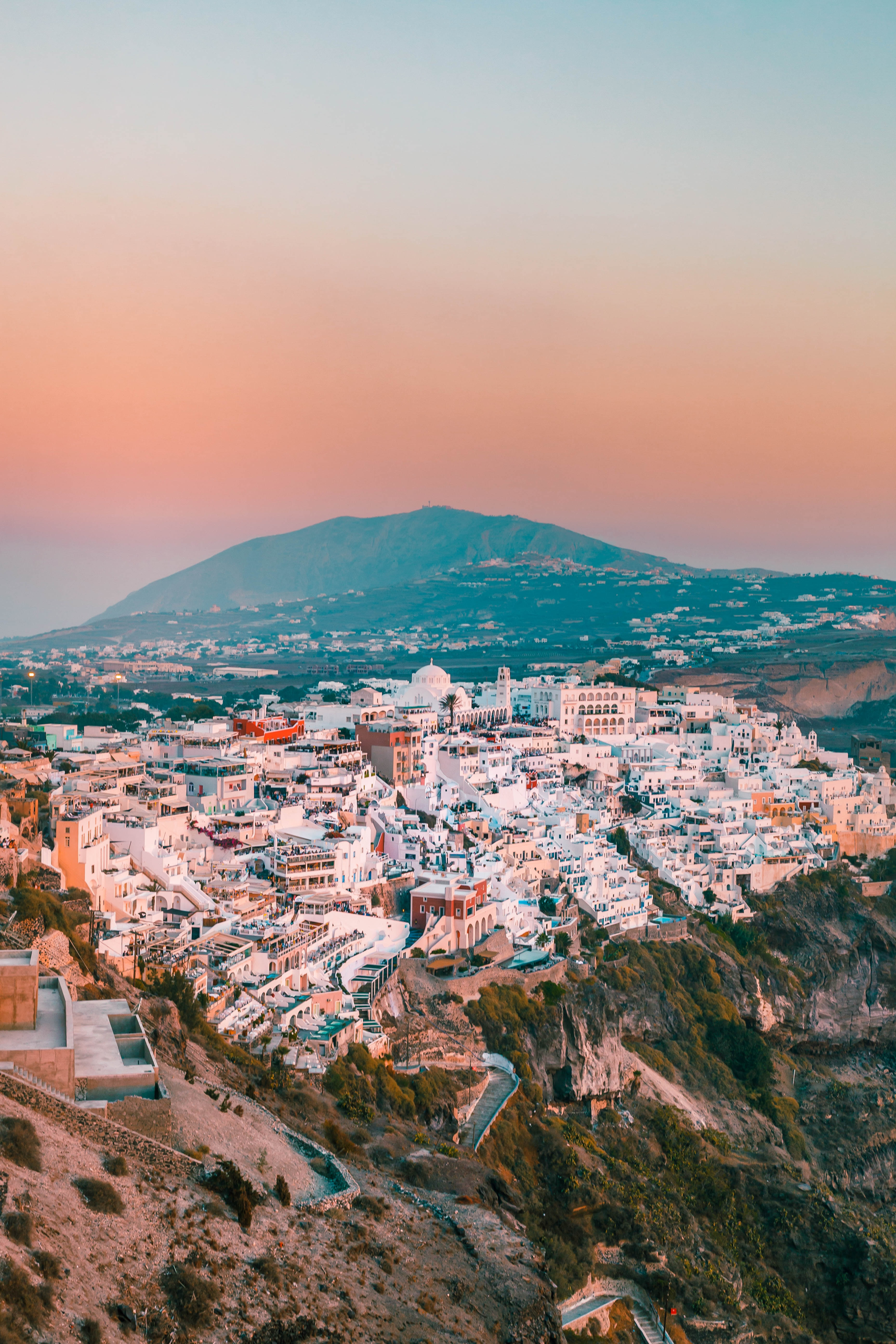 A Greek village built into a mountain side. In the background a dark mountain contrasts with the mostly white buildings below and the peach and light blue sky above.