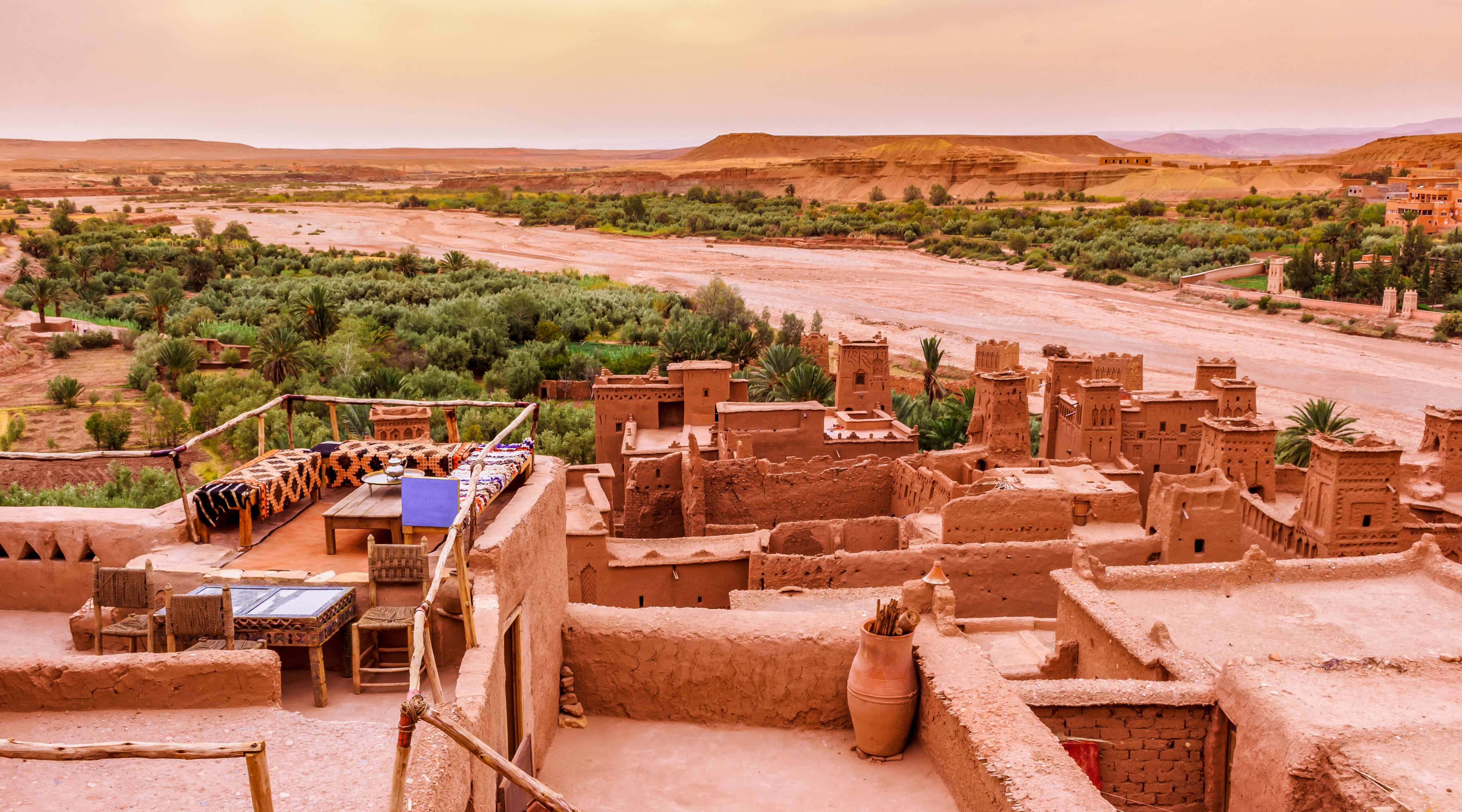 Overlooking Morrocan rooftop patios formed with red clay. Beyond them is more red dirt, some evergreen trees and a red butte.
