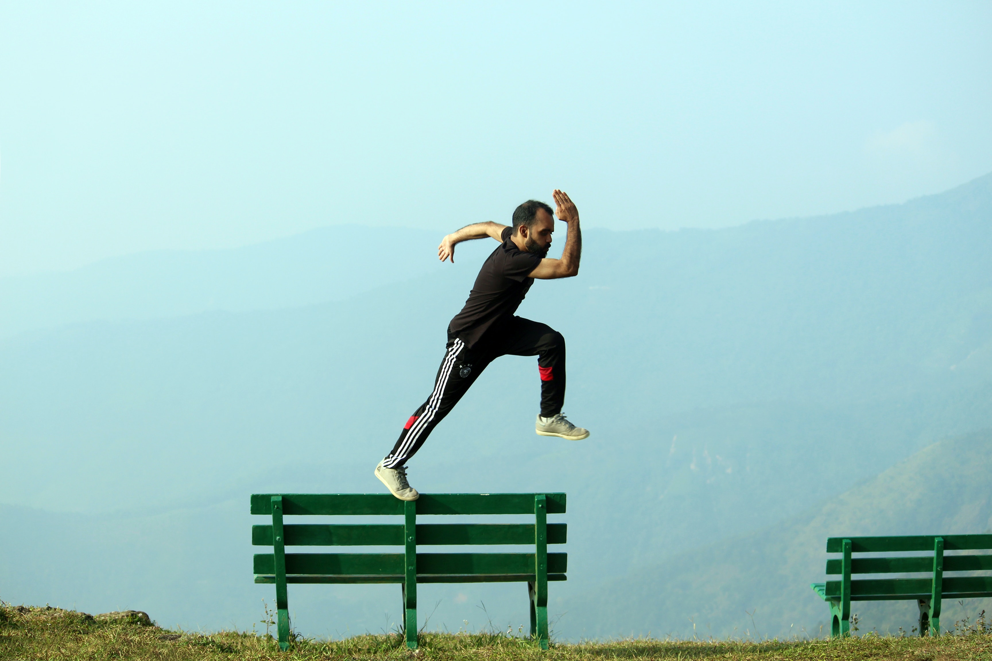 A man running across the back of a park bench looking like he is about to leap into the air. In the background is a mountain shrouded with mist with a deep valley below.