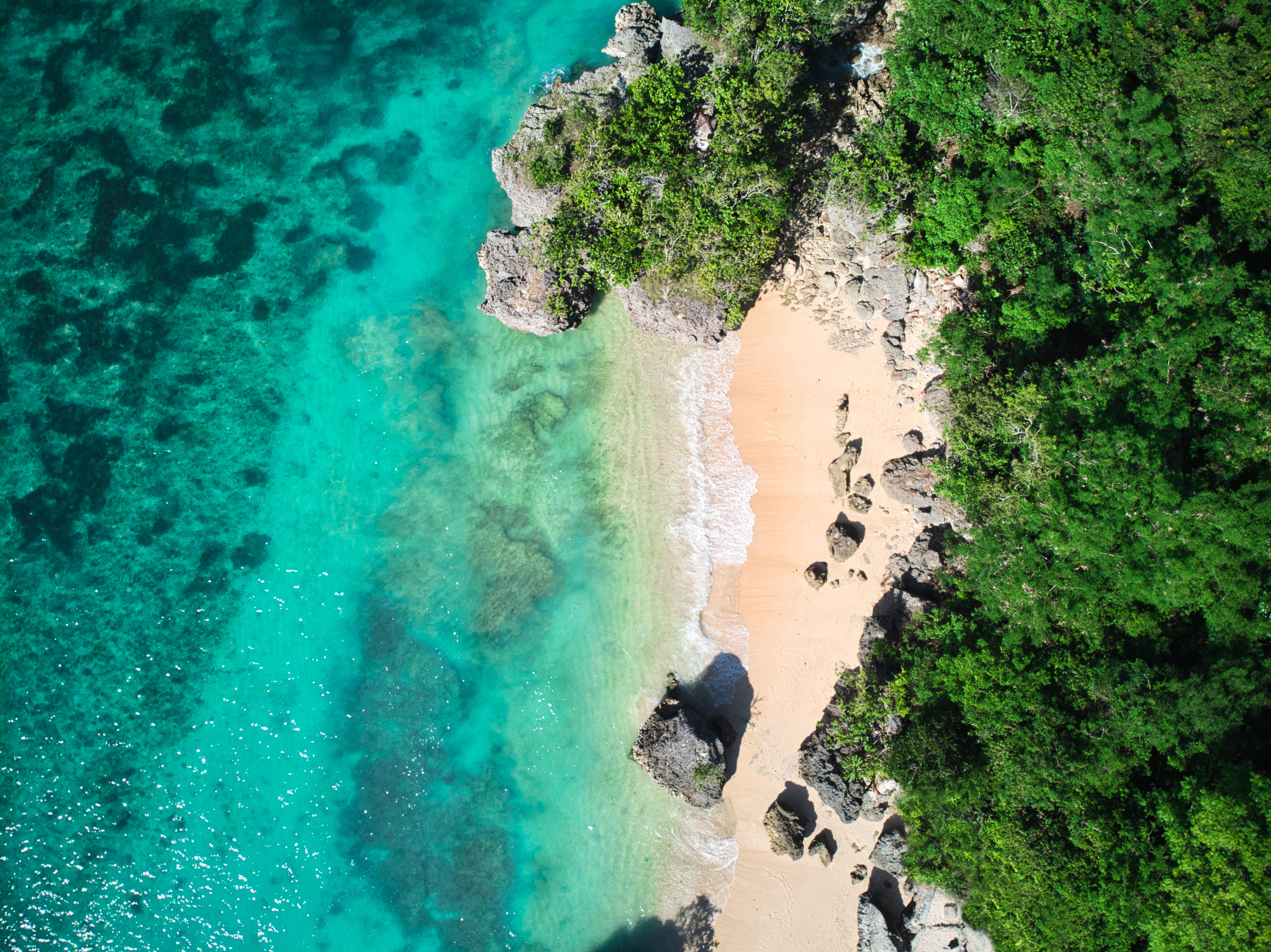 Looking down on a sandy beach with some large rocks in between a green forest and turquoise water.