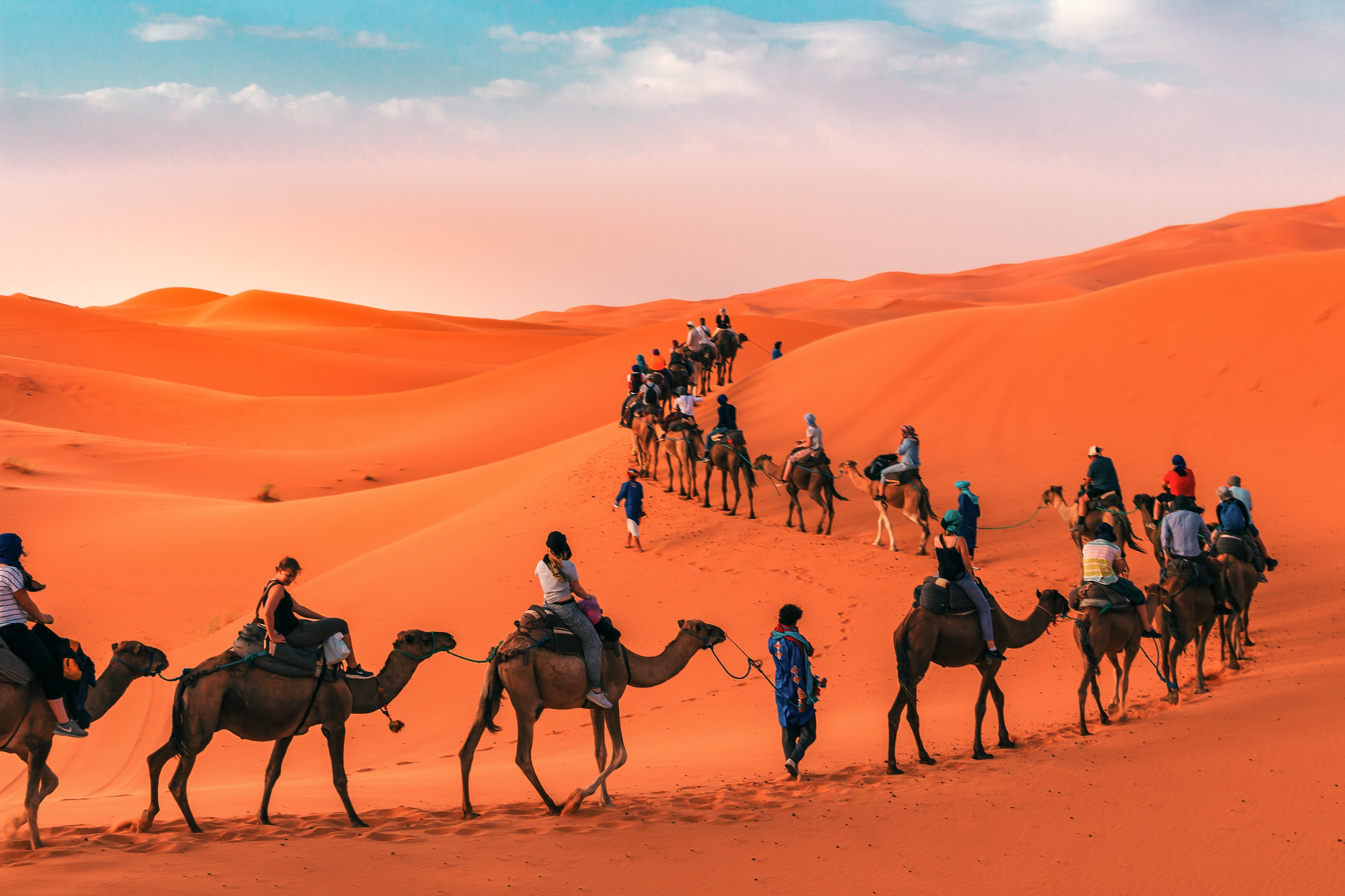 A camel train winding its way through the orange dunes of the Sahara Desert under a light blue sky with white clouds.