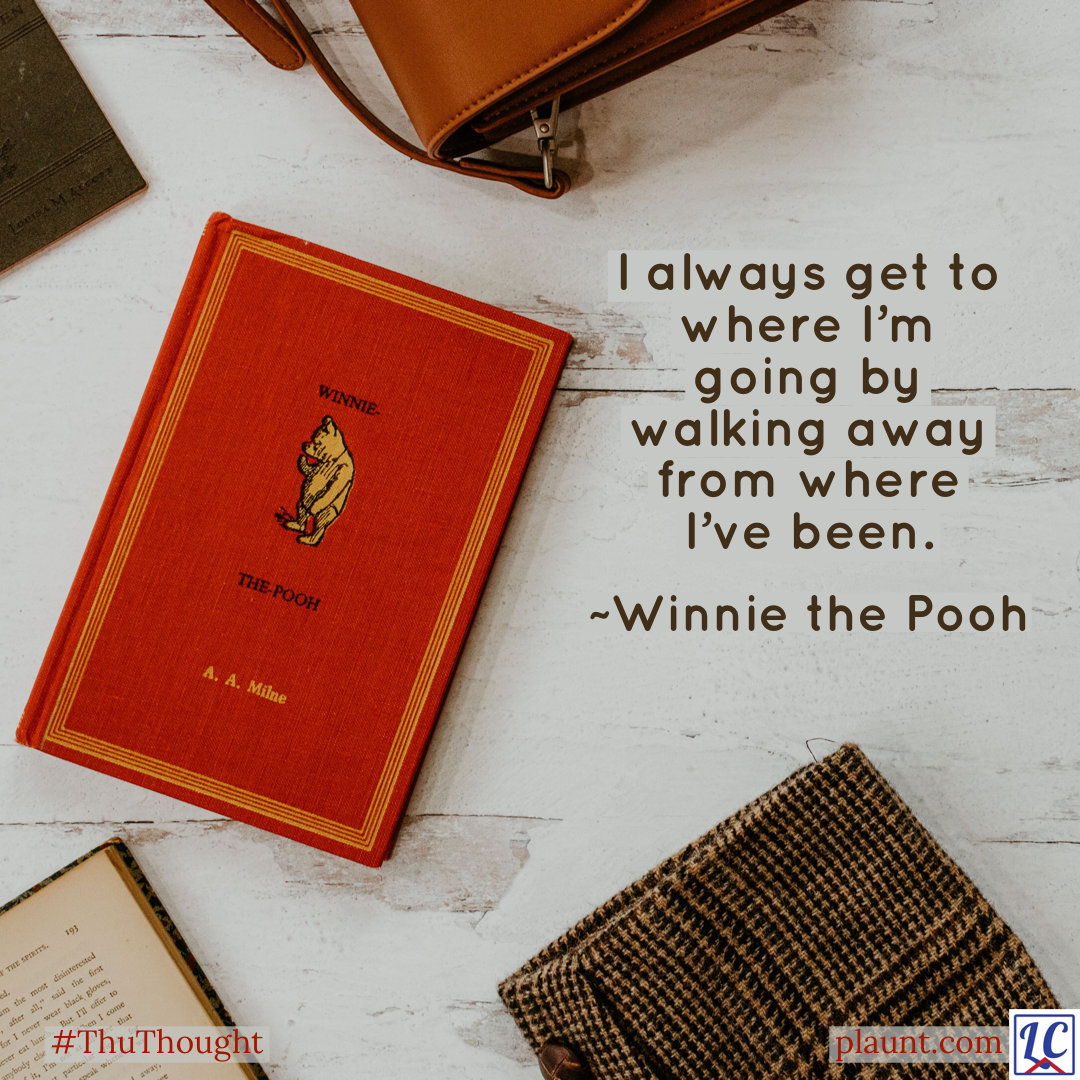 A red hardback copy of Winnie The Pooh by A. A. Milne sits in the middle of the photo on a grey wood table. The edges of other items--books, a tweed jacket, and a leather briefcase--are seen on the edges of the photo. Caption: I always get to where I'm going by walking away from where I've been. ~Winnie the Pooh