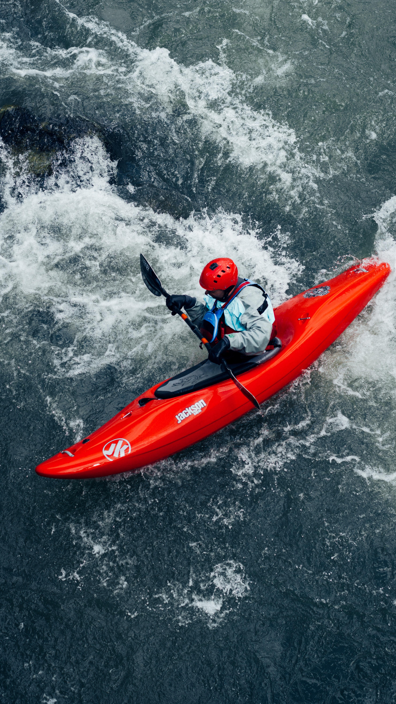 A paddler wearing a red helmet guiding a red kayak through rapids.