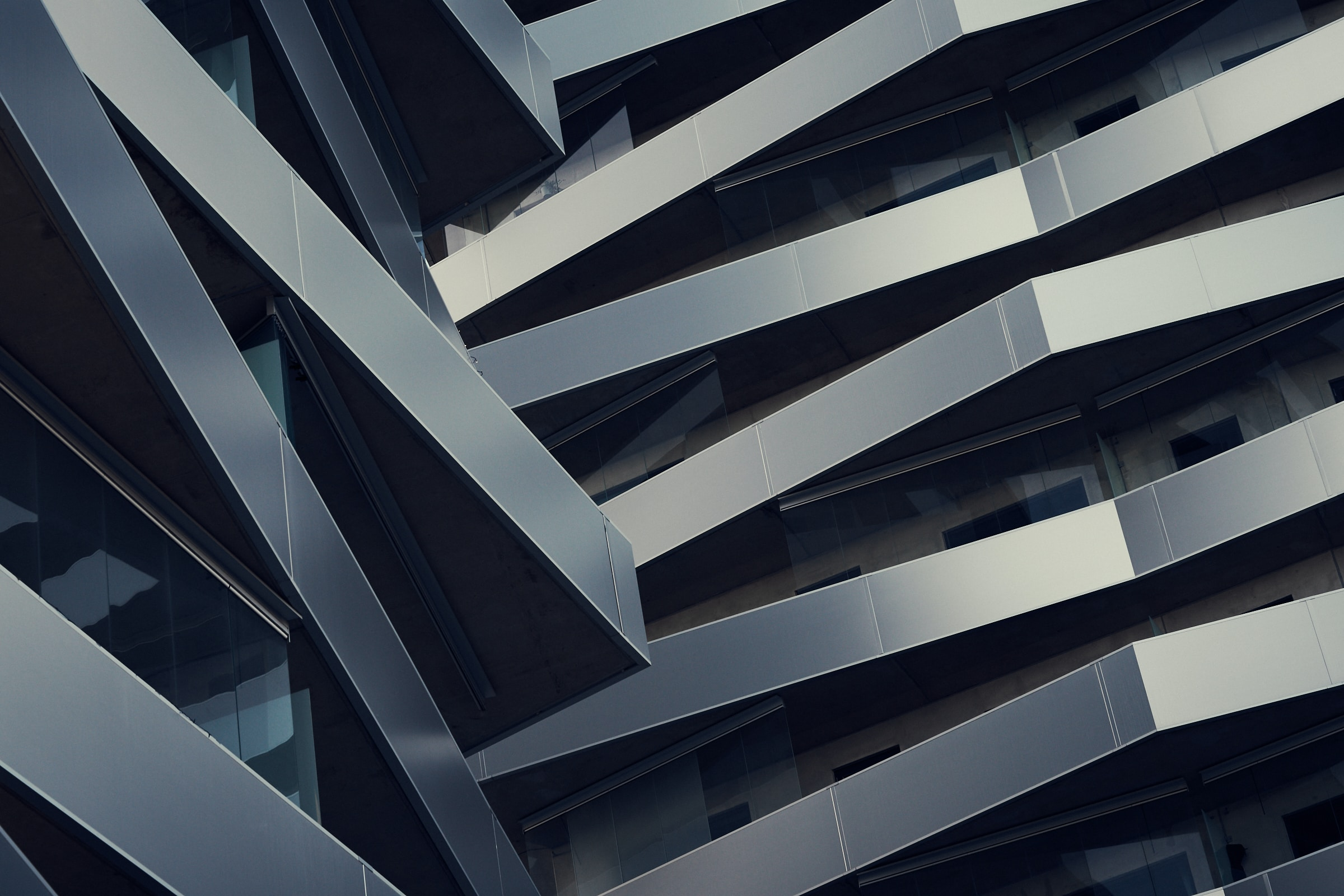 Balconies outside of a building made of steel that looks like it has been folded. The angle of the shot makes it all look very disorganized.
