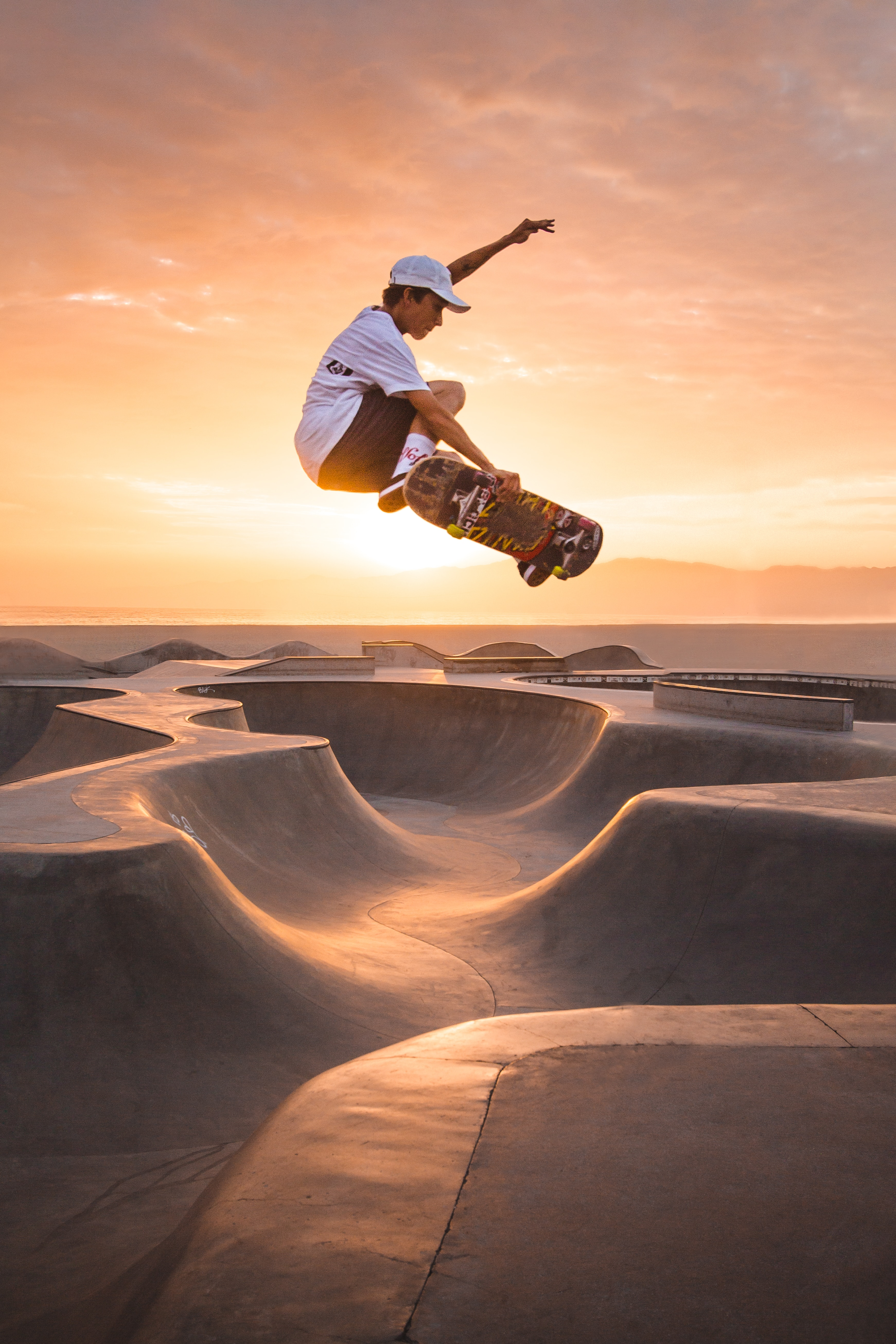 A skateboarder hanging in the air over the hills of a skate park with the sun setting in the background.