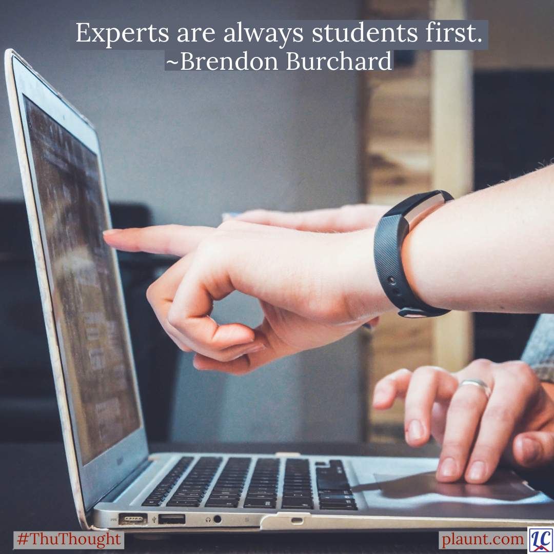 Two people pointing at a laptop monitor. Caption: Experts are always students first. ~Brendon Burchard